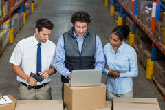 Warehouse workers and manager discussing with laptop. In the warehouse Stock Images