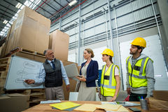 Warehouse workers and managers discussing plan on whiteboard Royalty Free Stock Images