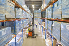 Warehouse workers moving boxes from shelf with forklift Royalty Free Stock Images