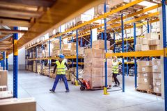 Warehouse workers pulling a pallet truck. Young warehouse workers pulling a pallet truck with boxes Royalty Free Stock Images