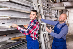 Warehouse workers taking frame from rack. Workmen in a warehouse are taking an aluminum window frame from a rack Royalty Free Stock Images