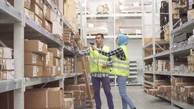 Warehouse workers communicate and carry out accounting scanner barcode. Warehouse workers at work communicate and carry out accounting scanner barcode stock footage
