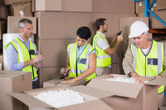 Warehouse workers in yellow vests preparing a shipment Stock Photos