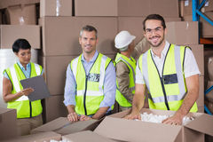 Warehouse workers in yellow vests preparing a shipment Royalty Free Stock Photo