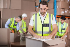 Warehouse workers in yellow vests preparing a shipment Stock Image