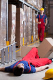 Warehouseman after accident at height. Vertical view of a warehouseman after accident at height Stock Images
