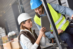 Warehouseman driving cart with coworker. Warehouseman driving cart, listening to operator instructions Stock Images