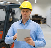 Warehouseman. Warehouseman in hard hat with tablet pc at warehouse Royalty Free Stock Images