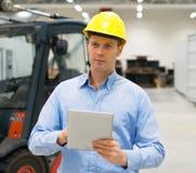Warehouseman. Warehouseman in hard hat with tablet pc at warehouse Royalty Free Stock Image