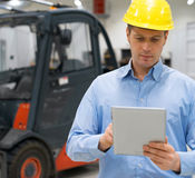 Warehouseman. Warehouseman in hard hat with tablet pc at warehouse Royalty Free Stock Photography