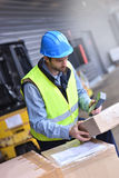 Warehouseman scanning delivered goods. Warehouseman on dock scanning products ready for shipment Royalty Free Stock Photos