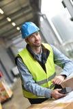 Warehouseman scanning merchandise. Portrait of warehouseman scanning merchandise on dock Royalty Free Stock Images