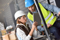 Warehouseman and store manager working. Warehouseman driving cart, listening to operator instructions Royalty Free Stock Photography