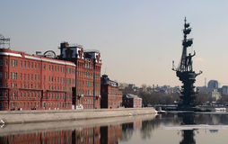 Warehouses and statue of Peter the Great. Brick warehouses next to the river with the statue of Peter the Great in the background Royalty Free Stock Photo