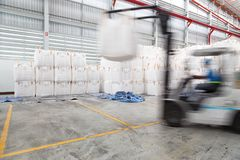 Warehousing. Forklift driver stacking big bag of raw material in Stock Photography