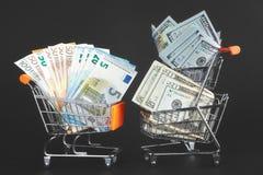 Warenkörbe mit rivalisierenden Währungen US-Dollar Rechnungen und Euro Stockfotografie