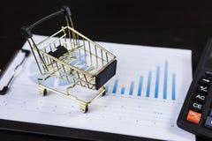 Warenkörbe mit Taschenrechner auf den Finanzdiagrammen Stockbilder