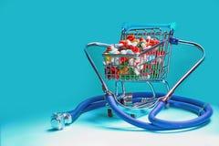 Warenkorb gefüllt mit Pillen mit einem Stethoskop Hintergrund für eine Einladungskarte oder einen Glückwunsch stockbild