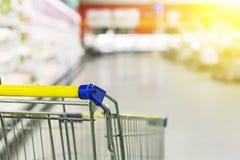 Warenkorb im Supermarkt Extrahieren Sie unscharfes Foto des Speichers mit Laufkatze in Kaufhaus bokeh Hintergrund Lizenzfreie Stockfotos