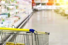 Warenkorb im Supermarkt Extrahieren Sie unscharfes Foto des Speichers mit Laufkatze in Kaufhaus bokeh Hintergrund Stockbild