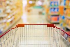 Warenkorb im Supermarkt-Gang und den Regalen Stockbild