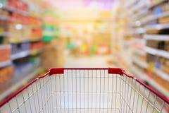 Warenkorb im Supermarkt-Gang und Regale in Unschärfe backgroun Stockbild
