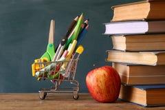 Warenkorb mit Schulbedarf, Apfel und Büchern Stockfotografie