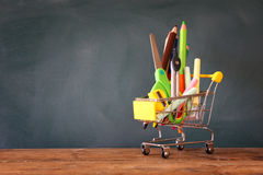 Warenkorb mit Schulbedarf vor Tafel lizenzfreie stockfotografie