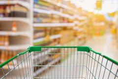 Warenkorb mit Supermarkt-Gang mit Produkt auf Regalen Stockbild