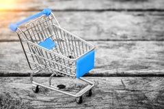 Warenkorb vom Gemischtwarenladen auf dem alten hölzernen Hintergrund Leere Einkaufenlaufkatze Stockfotos