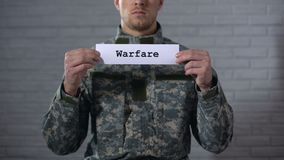 Warfare word written on sign in hands of male soldier, military conflict stock footage