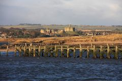 Warkworth Castle. With old wooden piers taken from Amble harbour Royalty Free Stock Photo