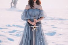 Warlike girl with dark hair in long gray vintage light dress, lady of cold and frost, bare open shoulders and sharp. Silver sword in hands, goddess of death royalty free stock photography