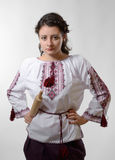 Resolute Ukrainian girl with a rolling pin. Warlike young woman is holding a rolling pin. She is wearing a shirt embroidered and a skirt Royalty Free Stock Photography