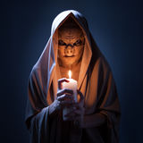 Warlock with candle in darkness. Royalty Free Stock Photos