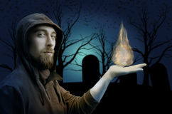 Warlock holding fire on cemetery background. Halloween concept. Gothic concept Royalty Free Stock Photography