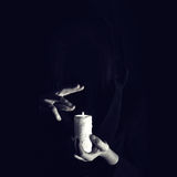 Warlock holds hands over burning candle in a darkness Royalty Free Stock Photo