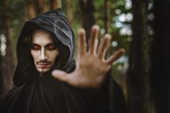 Warlock pointing finger. The black monk pointing his finger in the woods