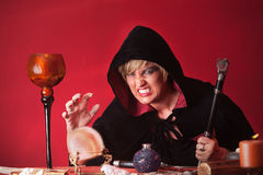Warlock With Spectre. Scary witch with sceptre and crystal ball over red background Royalty Free Stock Photos