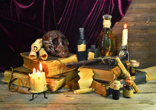 Warlocks magic objects. Halloween still life of old books, burning candles, skull and magic objects on wooden table Stock Image