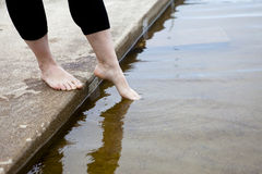 Is It Warm?. Female dipping her toes into the water Royalty Free Stock Photography