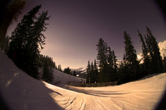Warm Alpine Slope. Fisheye shot of a skiing slope in the alps. Warm tones are intentional to create mood Royalty Free Stock Image