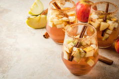 Warm apple sangria, apple cider. Autumn and winter drinks. Warm apple sangria, apple cider with pieces of fruit, cinnamon, spices, sugar. In glasses, on a stone stock images