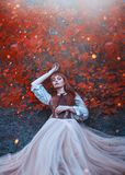 Warm art photo of sleeping beauty, girl with fiery red hair lies on ground in dense forest under orange leaves in bright royalty free stock photo