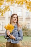 Warm atmospheric lifestyle photo of pretty woman with orange bouquet. The lady holds in her hand the yellow leaves. Sunny autumn concept stock image