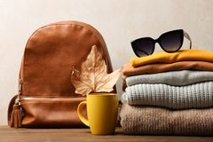 Warm autumn clothes. Backpack and warm clothes on wooden table on neutral background. Concept autumn clothes stock image