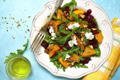 Warm autumn pumpkin salad with dried cranberries,arugula and feta on a vintage plate.Top view. Warm autumn pumpkin salad with dried cranberries,arugula and feta royalty free stock image