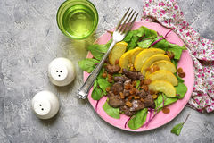 Warm autumn salad chard leaves,chicken liver,caramelized pear an. D raisins on a grey concrete or stone background.Top view Stock Images