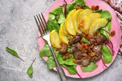 Warm autumn salad chard leaves,chicken liver,caramelized pear an. D raisins on a grey concrete or stone background.Top view Royalty Free Stock Photography
