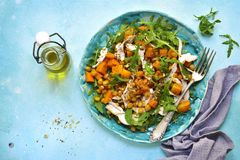 Warm autumn salad with pumpkin,chickpea,arugula and grilled chic. Ken on a plate over light blue slate,stone or concrete background.Top view Royalty Free Stock Photos